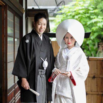 縁側での白無垢綿帽子の花嫁様と紋付羽織袴の新郎様