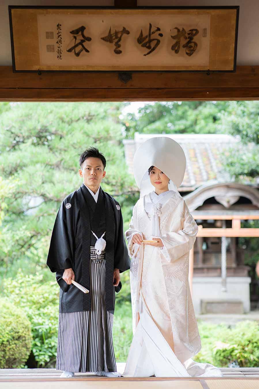 お庭をバックに立ち姿の白無垢と羽織袴の新郎新婦様