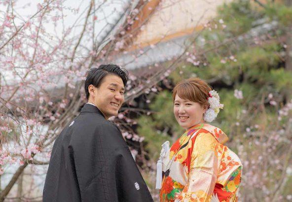桜をバックに手をつなぐ新郎新婦様