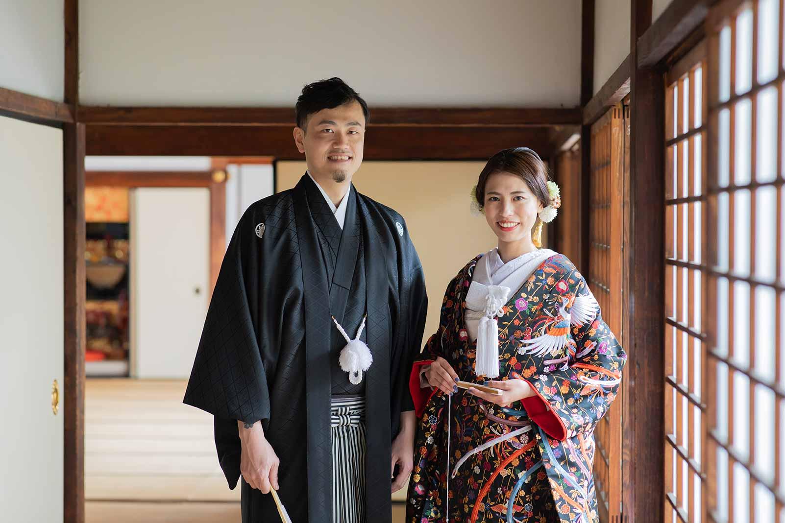 お寺の縁側で黒い色打掛と羽織袴のご夫婦様
