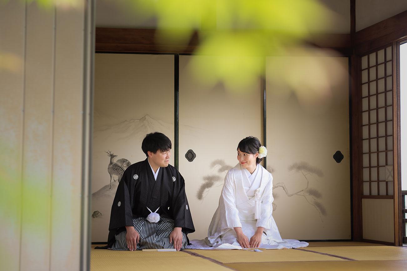 お寺の和室で見つめ合う正座姿の和装姿の新郎新婦様。