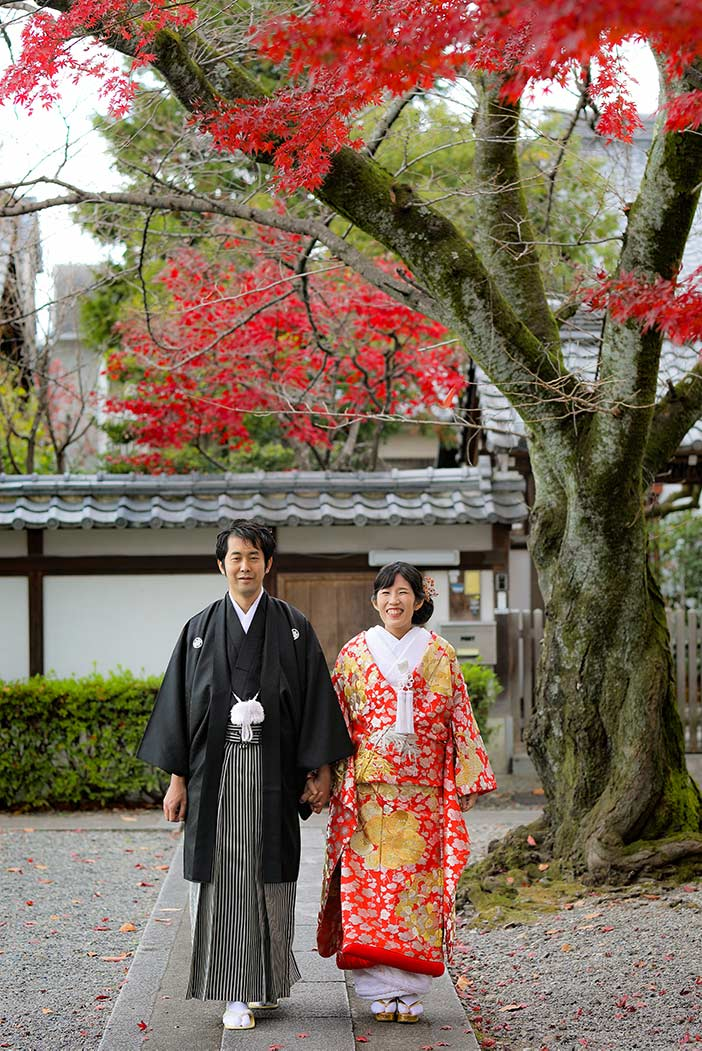 京都のお寺の境内で紅葉を背景に歩いている新郎新婦様