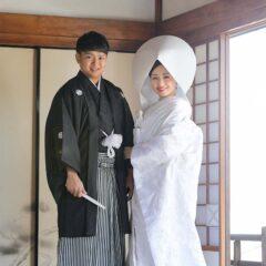 白無垢綿帽子姿で腕を組む新郎新婦様