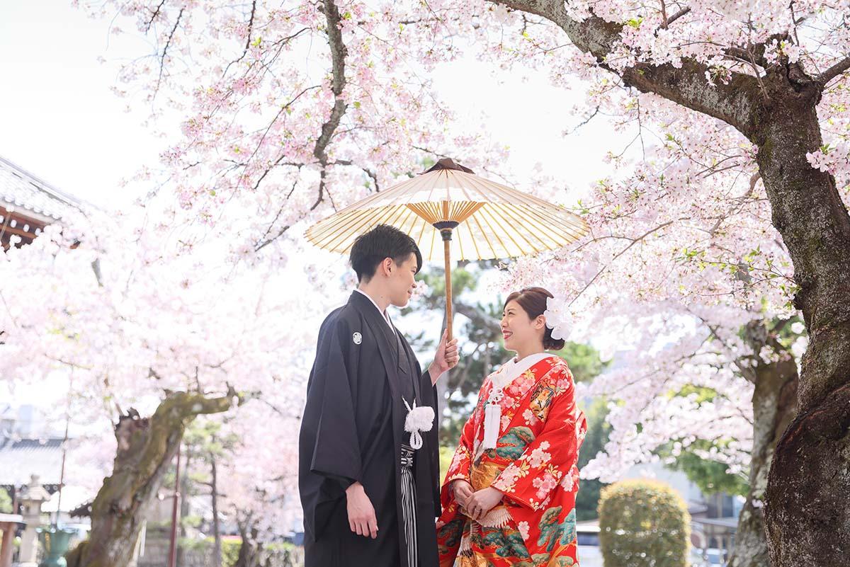 桜を背景に和傘の中で微笑み合う新郎新婦様