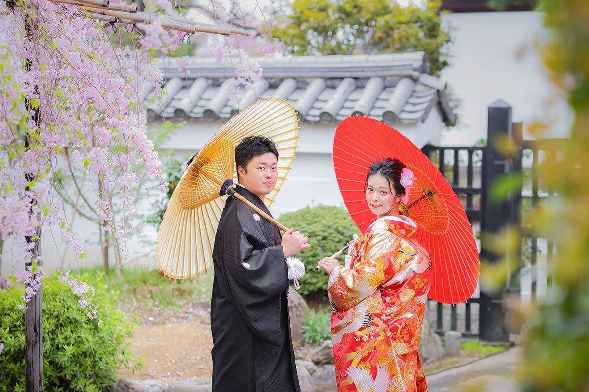 桜の下で番傘を使ったウェディングフォト