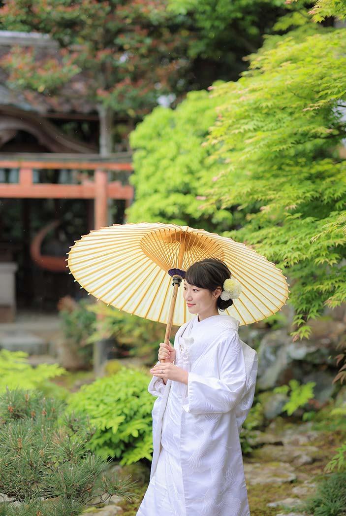 雨の日に番傘をさす白無垢姿の花嫁様
