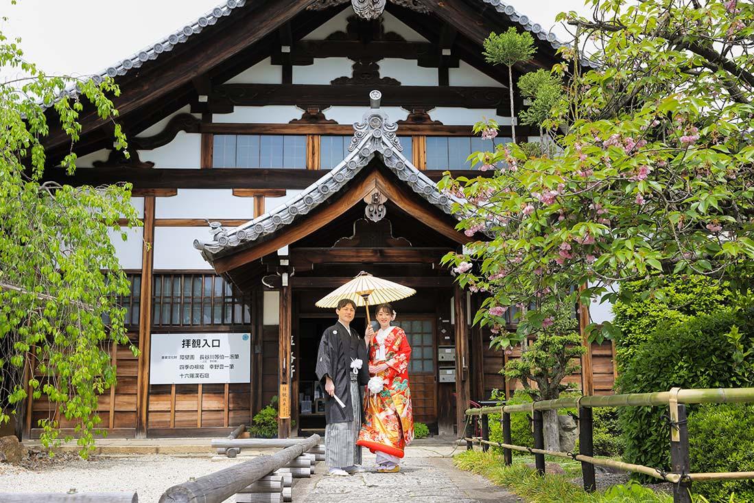 京都のお寺の本堂前にて和傘を使った結婚写真