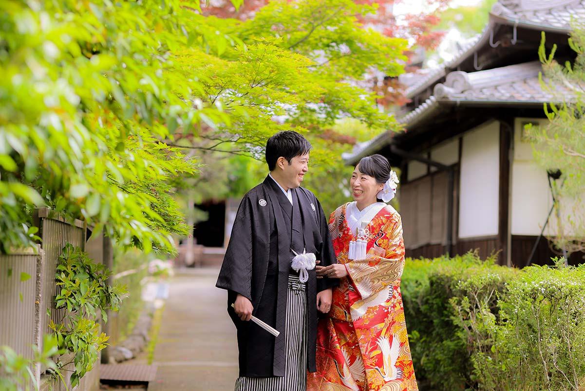 京都のお寺の境内で新緑を背景に手を取り合う新郎新婦様
