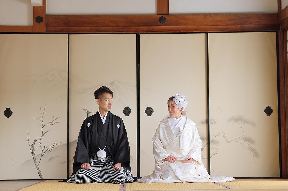 正座で見つめ合う白無垢・羽織袴の新郎新婦様