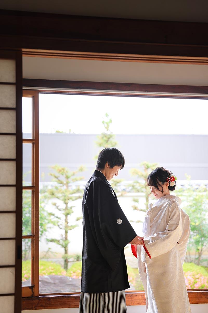 お庭を背景に手を取り合う和装前撮り写真