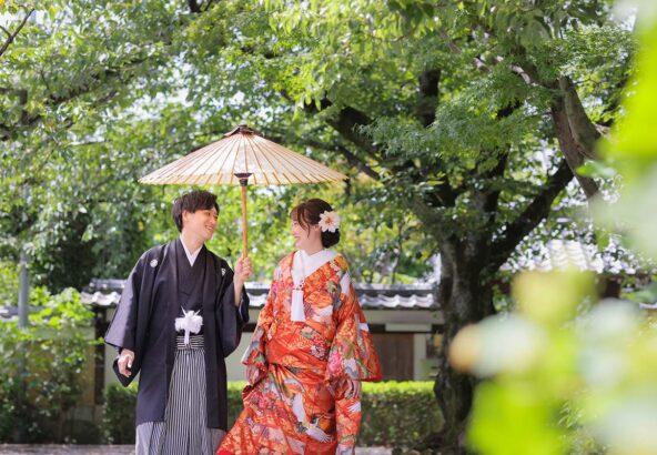 番傘を使って笑顔で歩く新郎新婦様