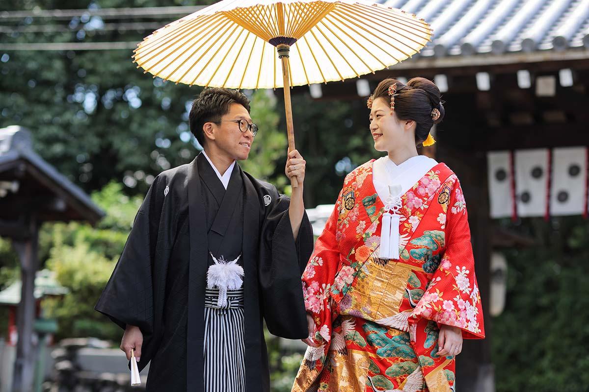 番傘を持って見つめ合う和装の新郎新婦様